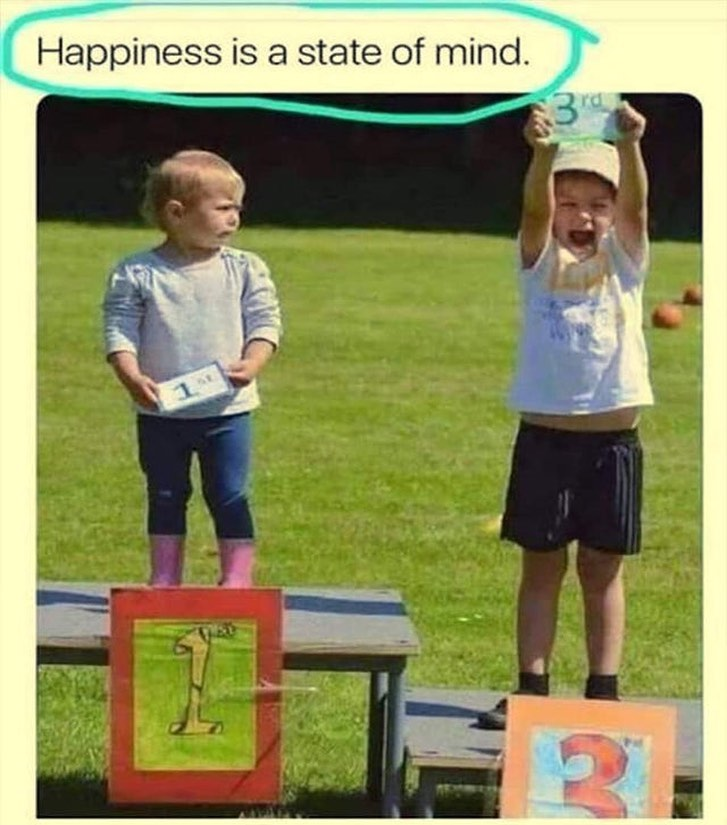 a child holding a 3rd place sign is visibly happier than the child holding the 1st place sign.